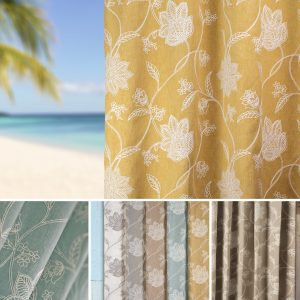 a view to a beach past an ochre coloured curtain with white flower embroidery