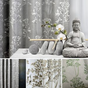 a budda sits in front of a grey curtain with silver embroidery